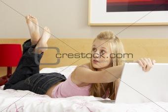 Guilty Teenage Girl Using Laptop In Bedroom