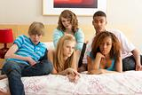 Group Of Five Teenage Friends Looking Bored In Bedroom