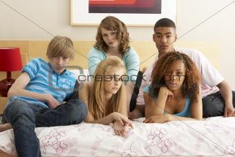 Group Of Five Teenage Friends Looking Bored In Bedroom