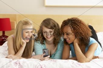 Group Of Three Teenage Girls Using Mobile Phone In Bedroom