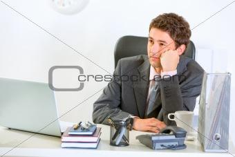 Bored modern businessman sitting at office desk