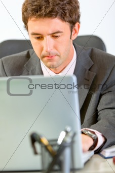 Portrait of modern businessman sitting at office desk and working on laptop