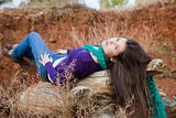 Shot of a young woman lying on log