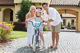 Family WIth Girl Riding Bike &amp; Happy Parents 