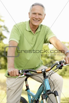 Portrait of man riding cycle in countryside