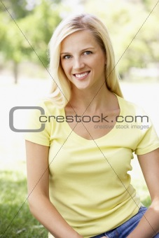 Portrait Of Young Woman Sitting In Park