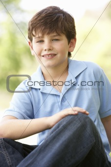 Portrait Of Young Boy Sitting In Park