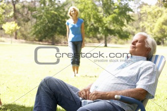 Senior Man Relaxing In Park With Wife In Background