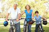 Grandparents And Grandson On Cycle Ride In Park