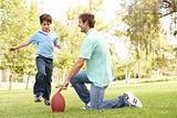 Father And Son Playing American Football Together