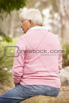 Back View Of Senior Man Sitting On Wall