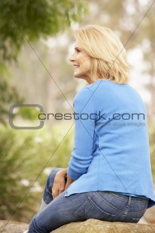Back View Of Senior Woman Sitting On Wall