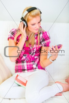 Happy young female sitting on sofa and listening music in headphones