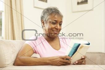 Senior Woman Reading Book At Home