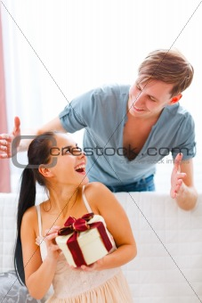 Happy young woman looking on boyfriend who made her surprise