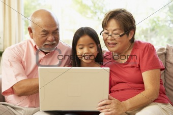 Grandparents And Granddaughter Using Laptop Computer At Home