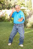 Senior Man Doing Tai Chi In Garden