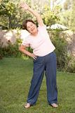 Senior Woman Exercising In Garden