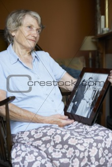 Senior Woman At Home Looking At Old Wedding Photo