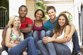 Group Of Friends Sitting On Steps Of Building