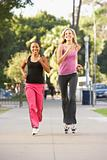 Two Female Friends Jogging On Street