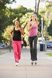 Two Female Friends Jogging On Street