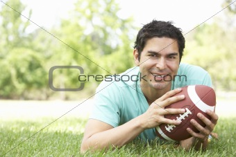 Portrait Of Young Man In Park With American Football