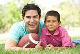 Father And Son In Park With American Football