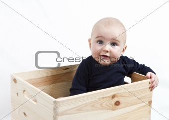toddler in wooden box