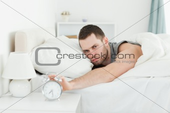 Tired young man switching off his alarm clock