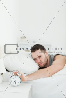 Portrait of a man being awakened by an alarm clock
