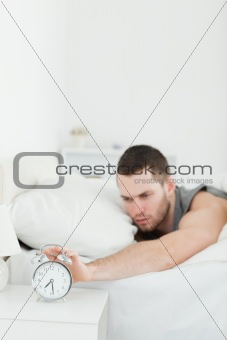 Portrait of a young man being awakened by an alarm clock