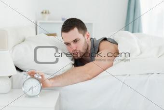 Tired man being awakened by an alarm clock