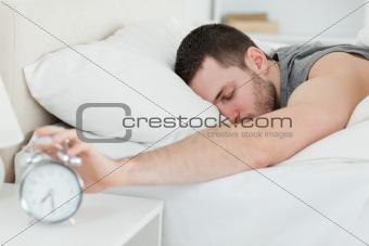 Sleeping man being awakened by an alarm clock