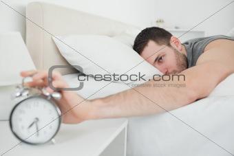 Sleeping attractive man being awakened by an alarm clock