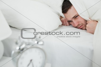 Tired man covering his ears while his alarm clock is ringing