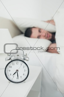 Portrait of an attractive young man covering his ears while his alarm clock is ringing