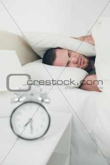 Portrait of a unhappy man covering his ears while his alarm clock is ringing