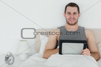Calm man using a tablet computer