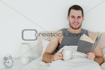 Man reading a novel while holding a cup of tea