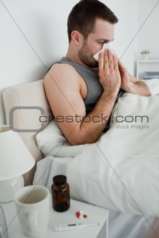 Portrait of a sick man blowing his nose