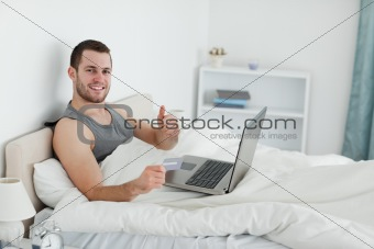 Happy man purchasing online with thumb up