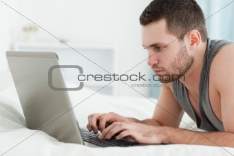 Focused man using a laptop while lying on his belly