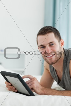 Portrait of an attractive man using a tablet computer while lying on his belly