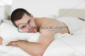 Attractive man lying on his belly