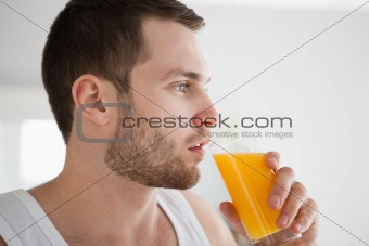 Close up of a healthy man drinking orange juice