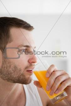 Close up of a man drinking orange juice