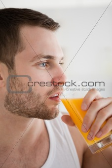 Close up of a young man drinking orange juice