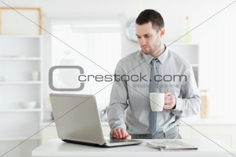 Businessman using a laptop while drinking coffee