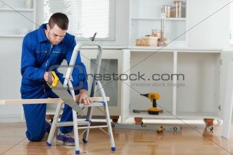 Handyman cutting a wooden board